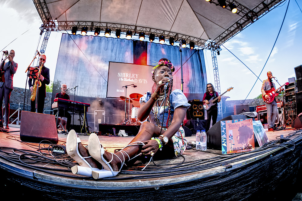 Davis desatándose los zapatos sobre el escenario